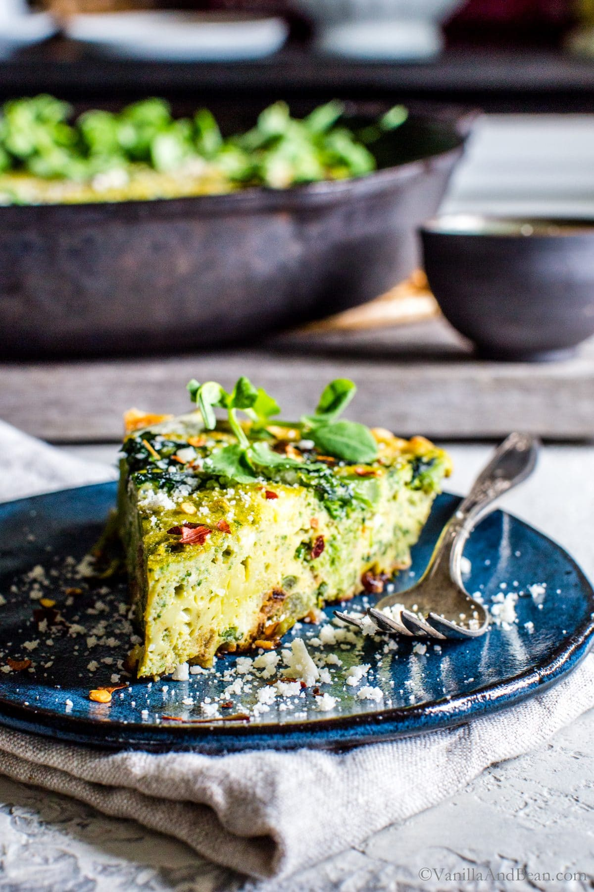 A slice of Broccoli Rabe Frittata with Pesto Ricotta on a serving plate sprinkled with parmesan.