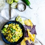 Overhead shot of Mango Avocado Salsa served with chips, lime and something refreshing to drink.