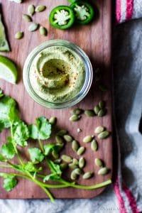 Overhead shot of Chili-Lime Pepita Crema in a jar, on a board.