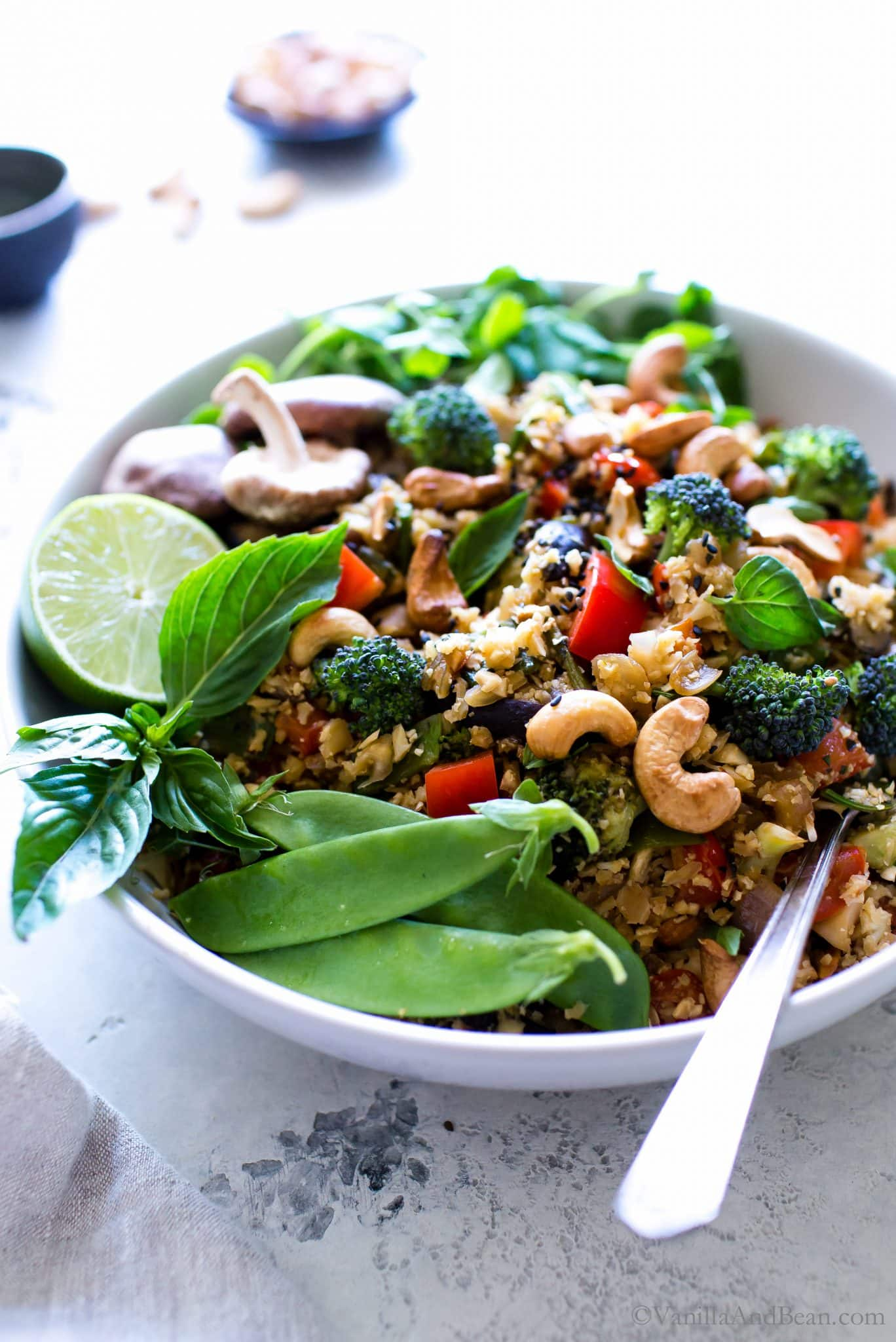 Vibrant, nourishing, and packed with umami flavors, Thai Vegetable Cauliflower Fried Rice with Cashews comes together with ease and makes a hearty Thai inspired dinner. Top it with an optional fried egg or prepared tofu to stretch this main further. #CauliflowerRice #PlantBased #Vegetarian #Vegan #GlutenFree