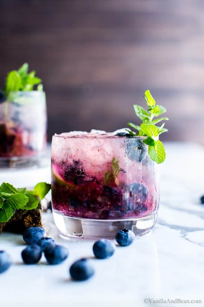Fresh Blueberry Mojitos in a cocktail glass with a sprig of mint.