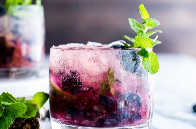 Something I look forward to every summer: fresh Blueberry Mojitos! A white rum cocktail that's easy to make, minty and super refreshing! #RumCocktail #Cocktail #Mojito #WhiteRumCocktail
