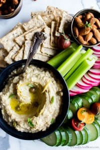 Overhead shot of Roasted Eggplant Artichoke White Bean Dip shared with fresh veggies, olives and nuts.