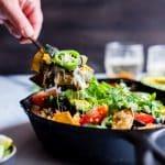 A spoon digging into Skillet Black Bean Vegetarian Enchiladas Verde.