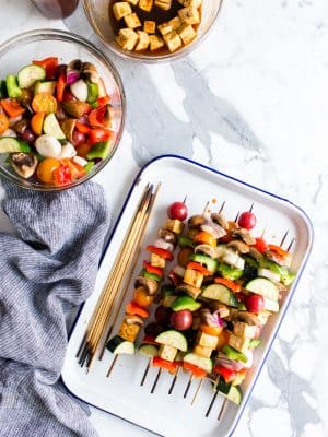 Overhead shot of Grilled BBQ Tofu Vegetable Kebabs on a pan with a brush of BBQ sauce ready to eat.