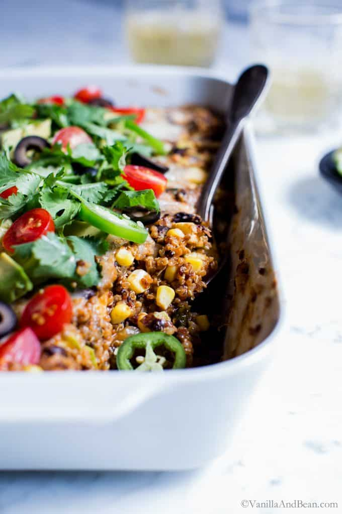 Close up of Quinoa Enchilada Casserole with a spoon ready to be shared.