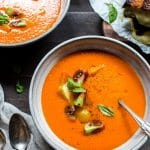 Roasted Red pepper and tomato soup in serving bowls, garnished with tomatoes and basil.