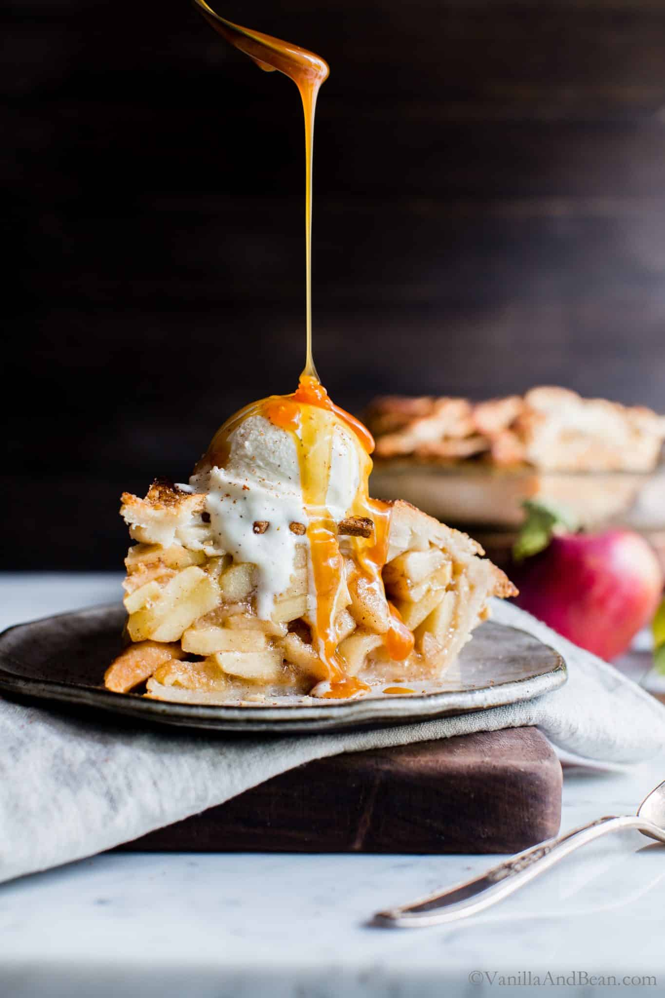 Apple Pie with ice cream on top and a drizzle of caramel sauce on a plate.