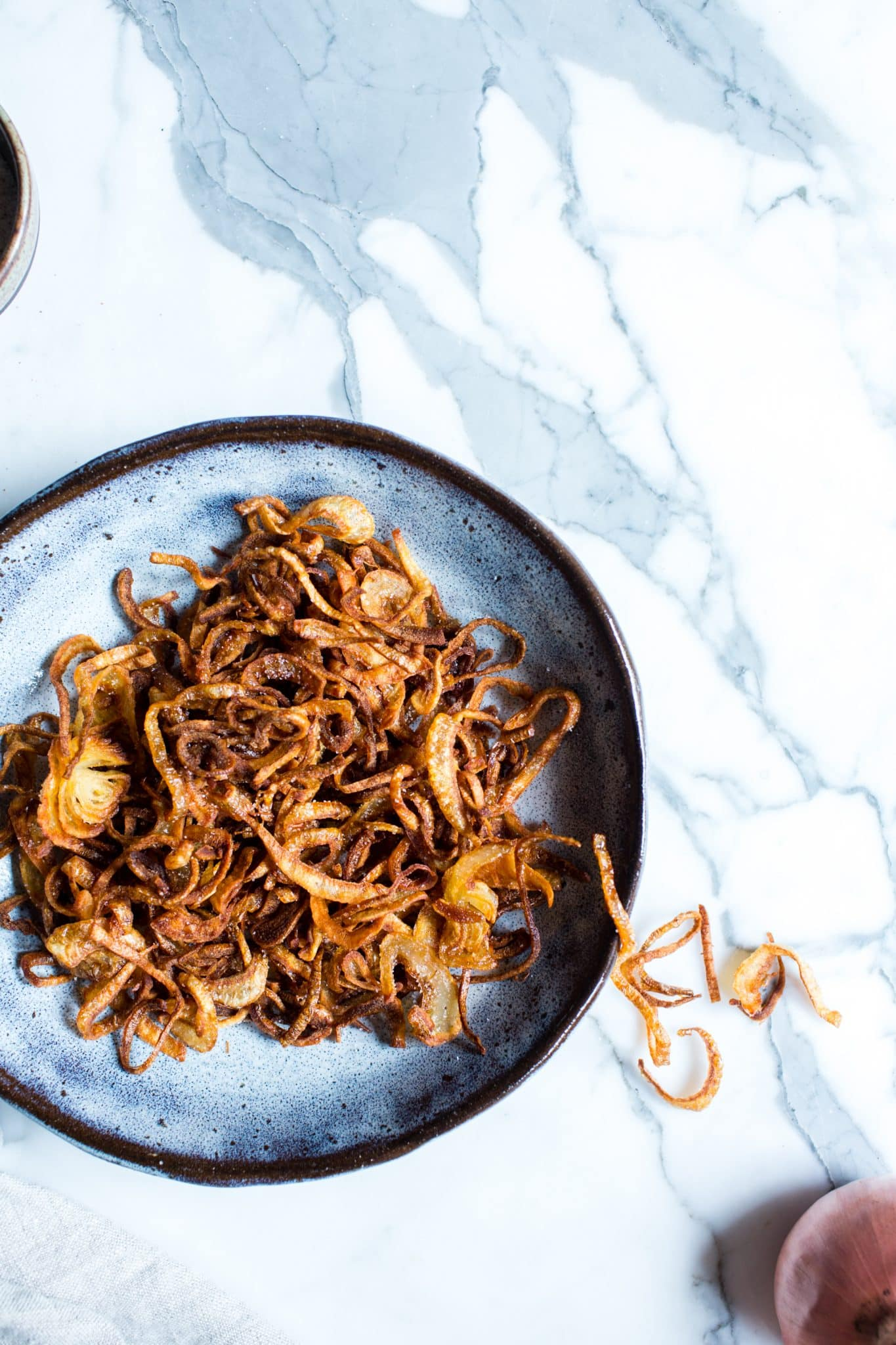 Overhead shot of crispy shallots in a bowl.