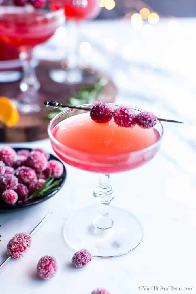Smooth, tart and a bit of sweet, this cranberry juice cocktail is muddled with fresh cranberries for the brightest flavors. A hint of rosemary gives this cranberry juice cocktail just a bit of intrigue. Cranberry-Orange Gin Smash is party pleasing! #HolidayCocktail #HappyHour #GinCocktail #AdultBeverave #CranberryJuiceCocktailRecipe #CranberryOrangeCocktail