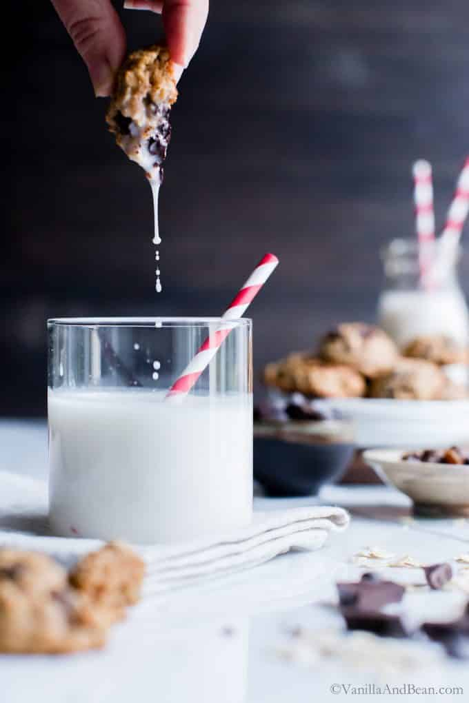Healthier Oatmeal Cookie dunked into a glass of milk.