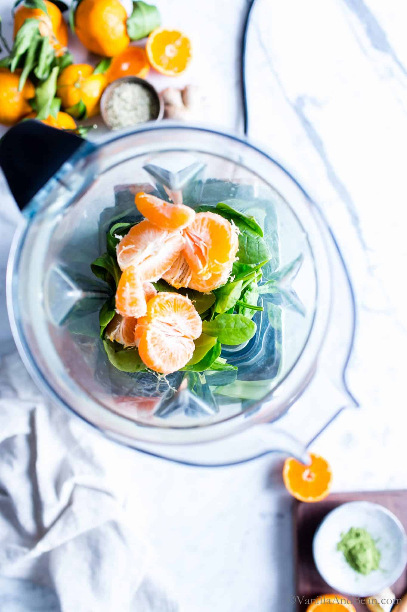 Spinach and oranges in a high speed blender container