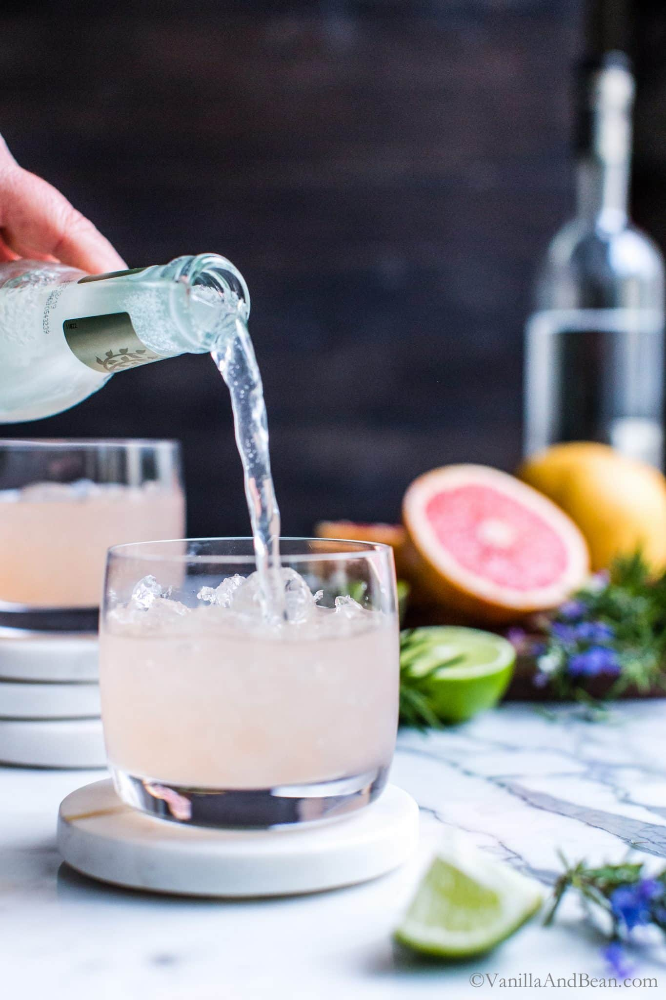 Pouring ginger beer into fresh grapefruit Moscow mules in a cocktail glass.