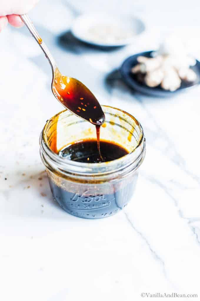 Ginger-Garlic Teriyaki Sauce in a jar with a spoon drizzling the sauce in.