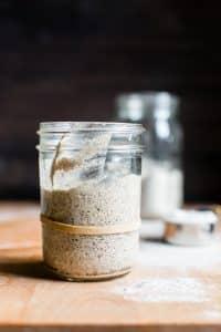A ripe, doubled in size gluten free sourdough starter in a jar.