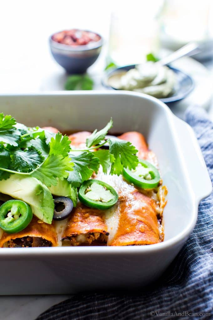 Baked Veggie Enchiladas garnished with olives, peppers, cilantro and avocado.
