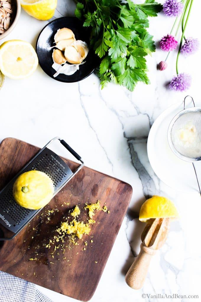 Zesting lemons for the lemon garlic dressing.