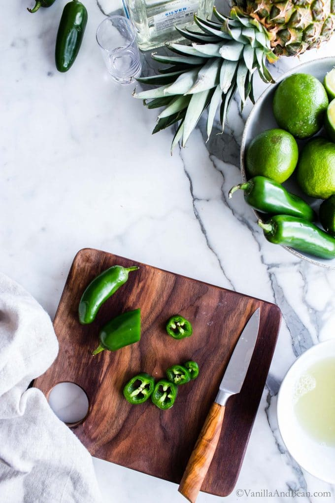 Slicing jalapenos on a cutting board.