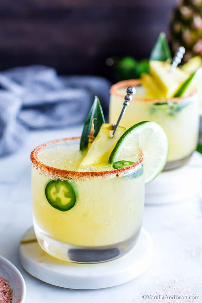 Pineapple Jalapeno Margarita garnished with lime, pineapple and jalapenos with a smoky paprika and sugar rim. .
