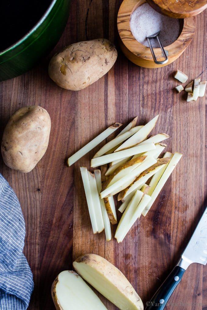 Thin batons of cut potatoes on a cutting board.