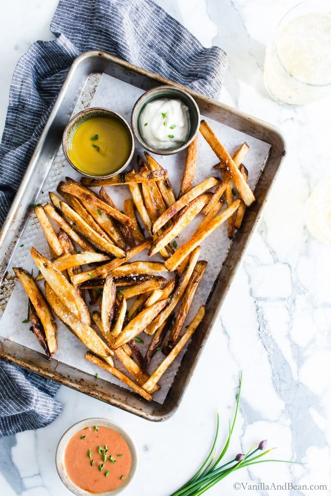 Crispy Oven Fries in a tray served with a few difference sauces on a pan ready to share.