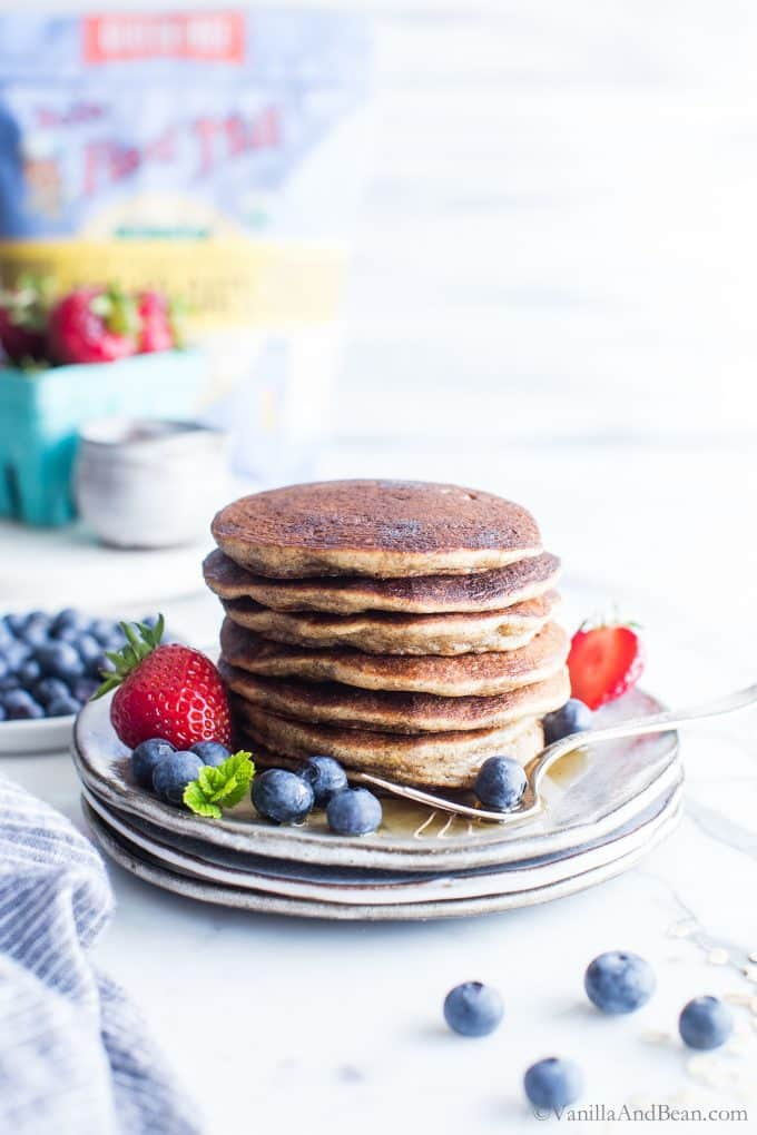A Stack of Gluten Free Sourdough Pancakes on a plate with berries.