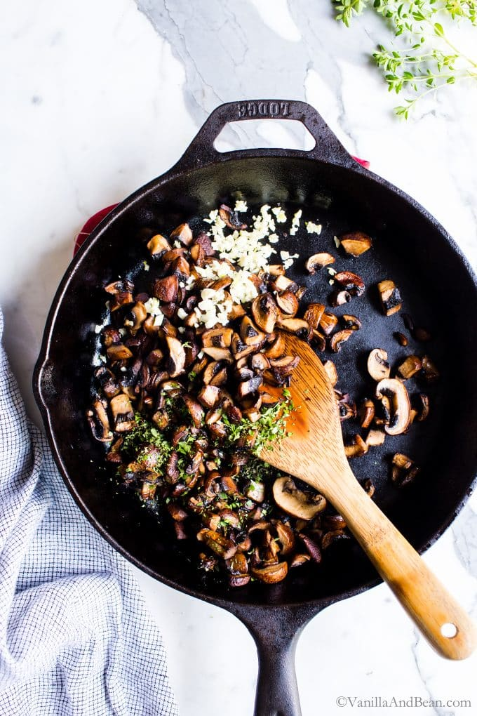 Mushrooms, garlic and thyme in skillet with a spoon.