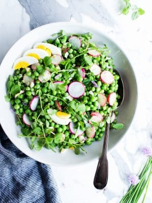 Healthy Pea Salad in a large bowl with a spoon ready to be served.