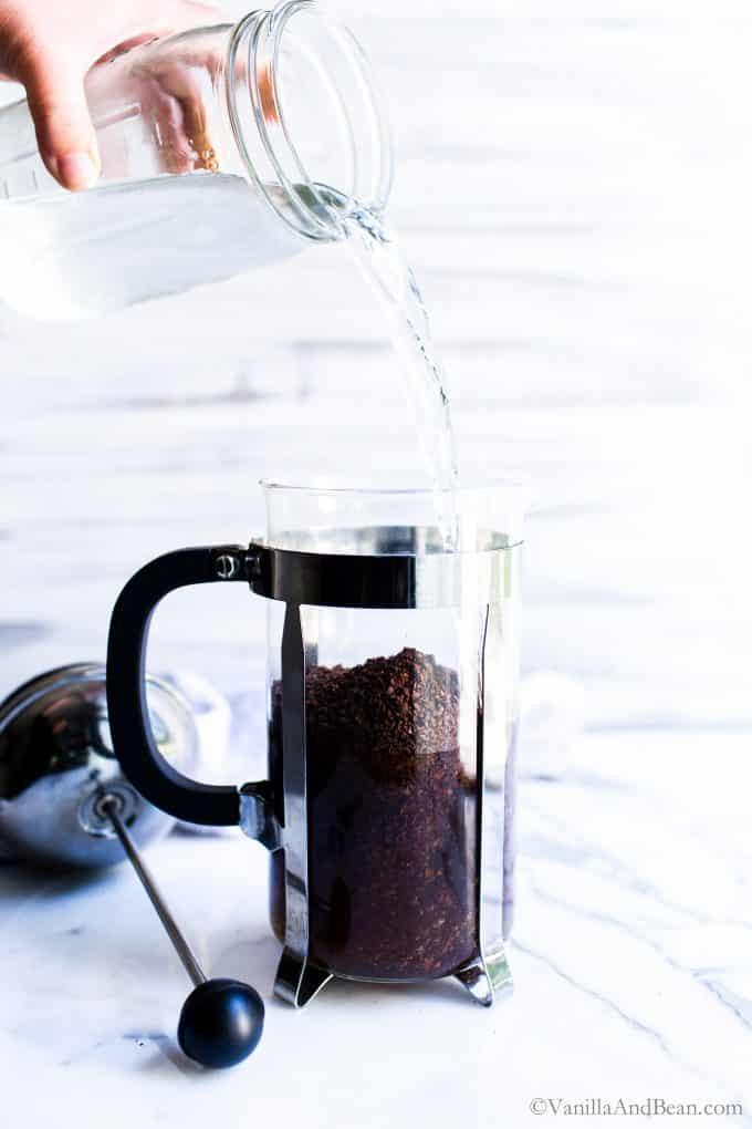 Pouring a jar of water into the French press.