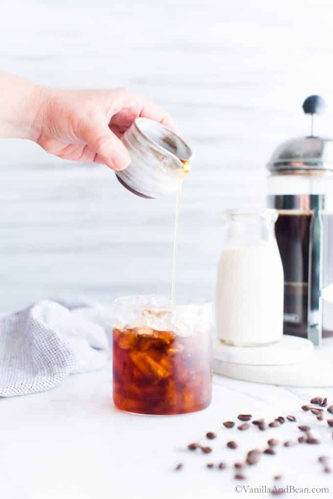 Pouring maple syrup into a glass of iced cold brew.