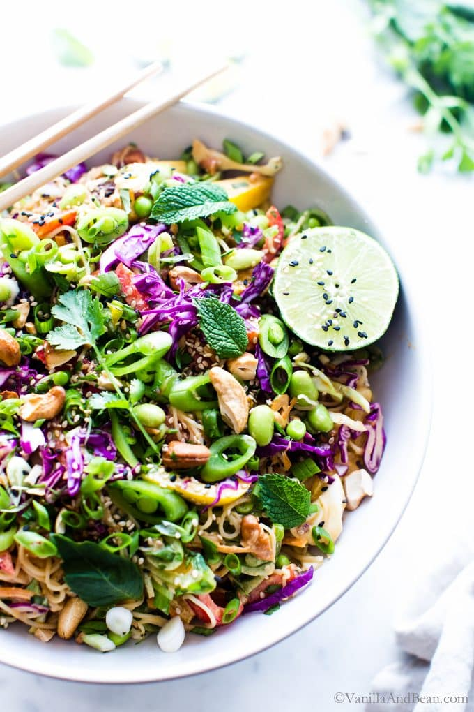 Cold Peanut Noodles Salad in a large serving bowl garnished with lime and herbs.