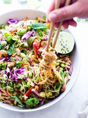 Peanut Noodle Salad in a serving bowl with chopsticks twirling the noodles.