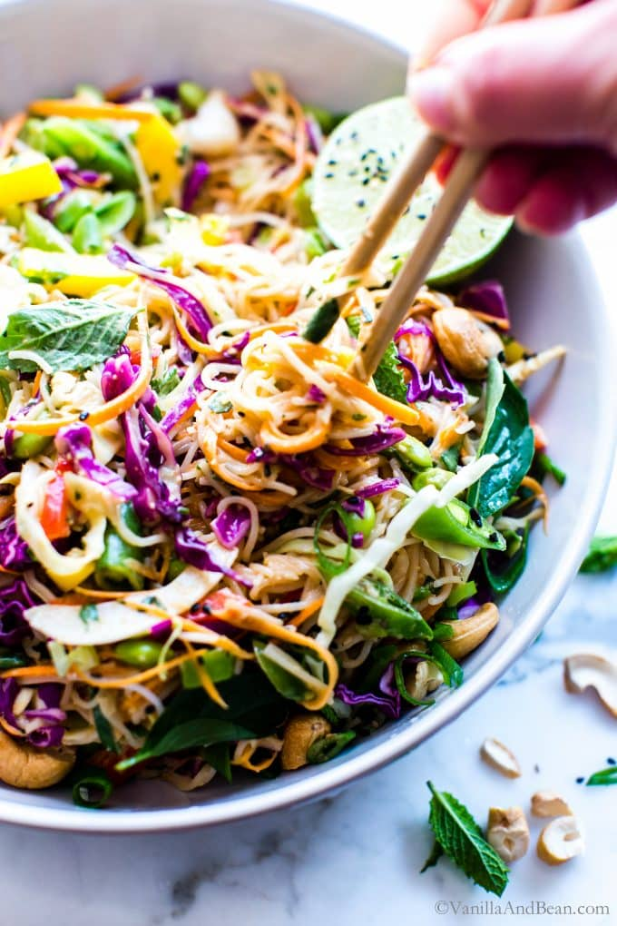 Peanut Noodle Salad in a serving bowl with chopsticks twirling the noodles.