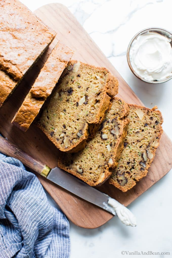 Maple Sweetened Zucchini Bread sliced on a cutting board served with cream cheese.
