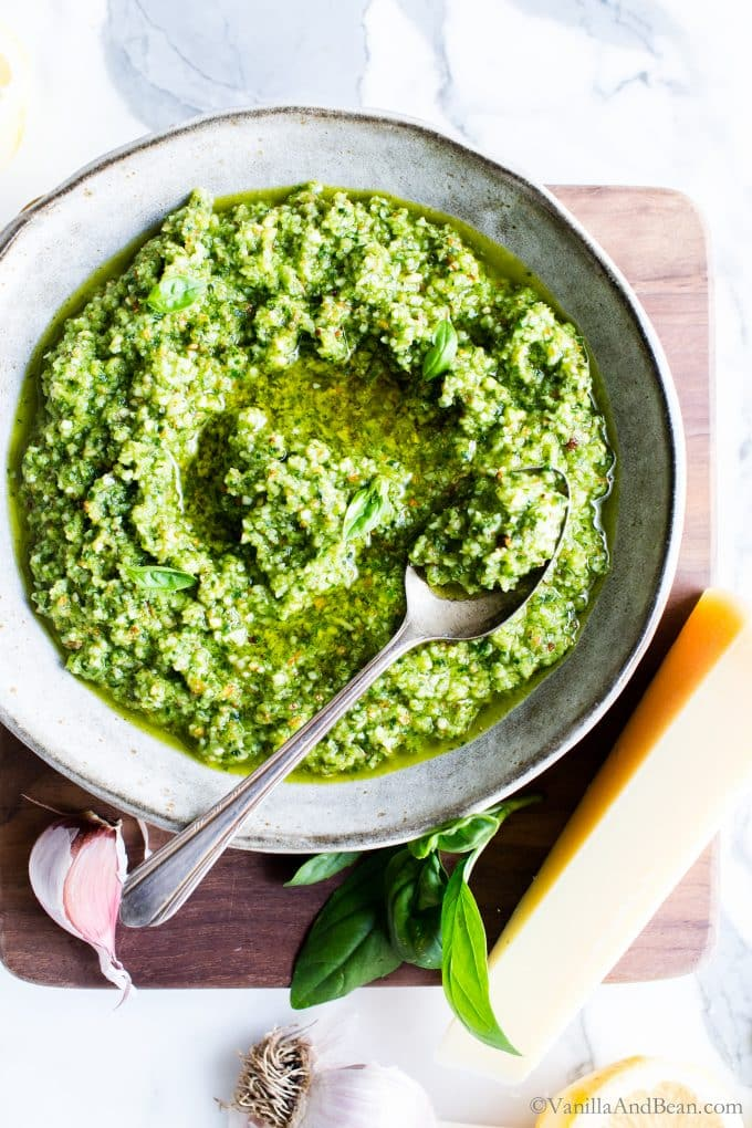Almond basil pesto in a bowl with a spoon.