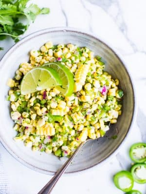 Chili Corn Salsa in a bowl in a bowl garnished with lime wedges.