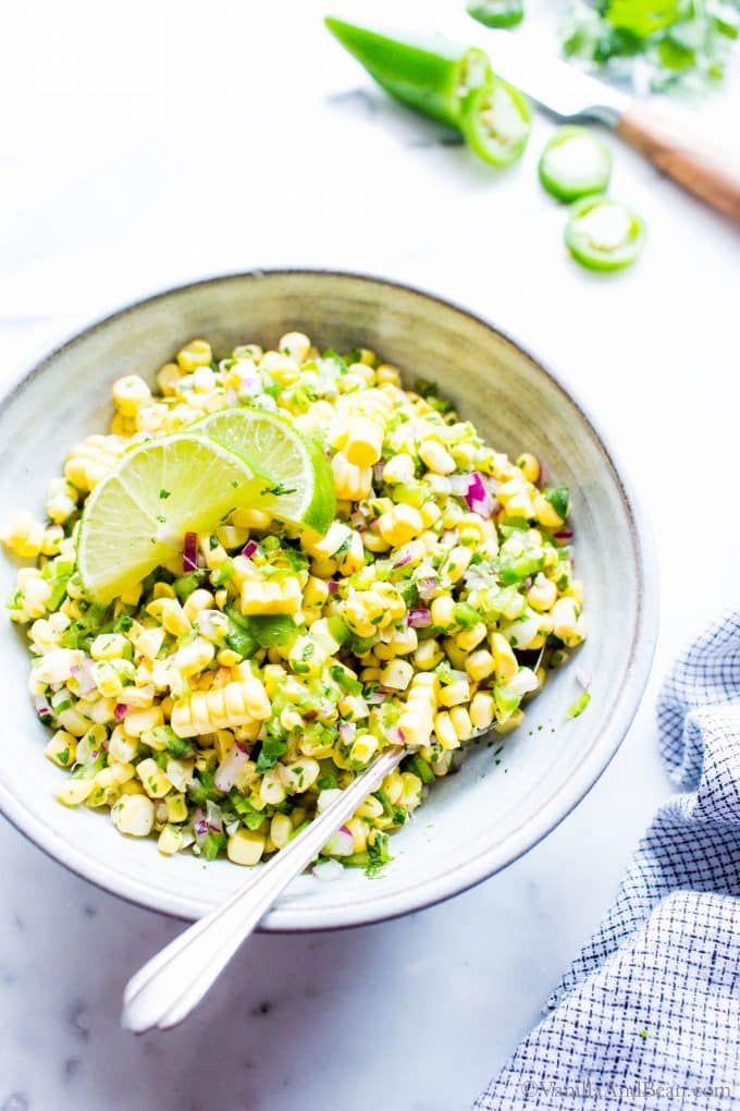 Corn Salsa in a bowl garnished with limes.
