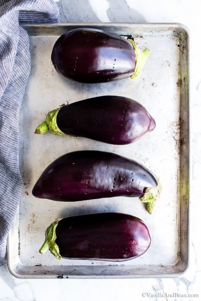 Cut eggplants on a parchment lined sheet pan.
