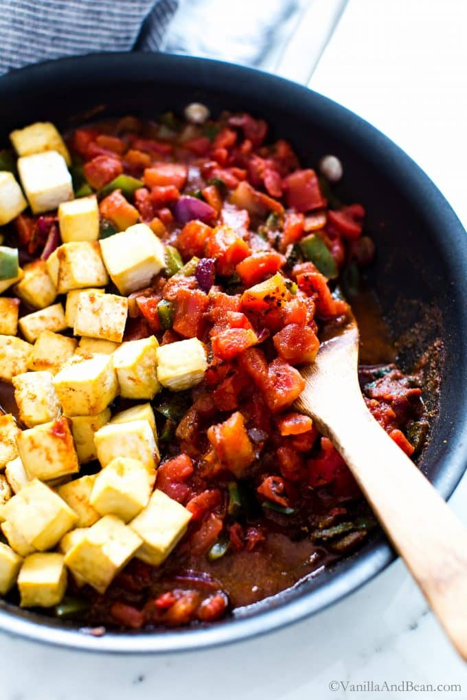 Tofu, tomatoes and spices in a pan with peppers and onions.