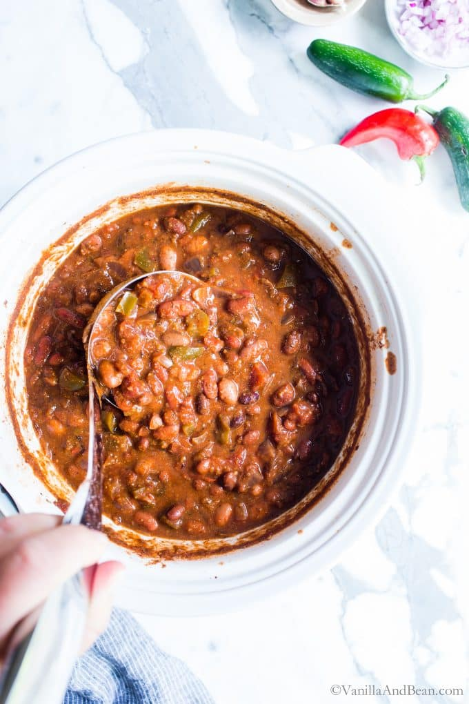 Vegetarian chili in a crock pot being scooped out with a ladle.