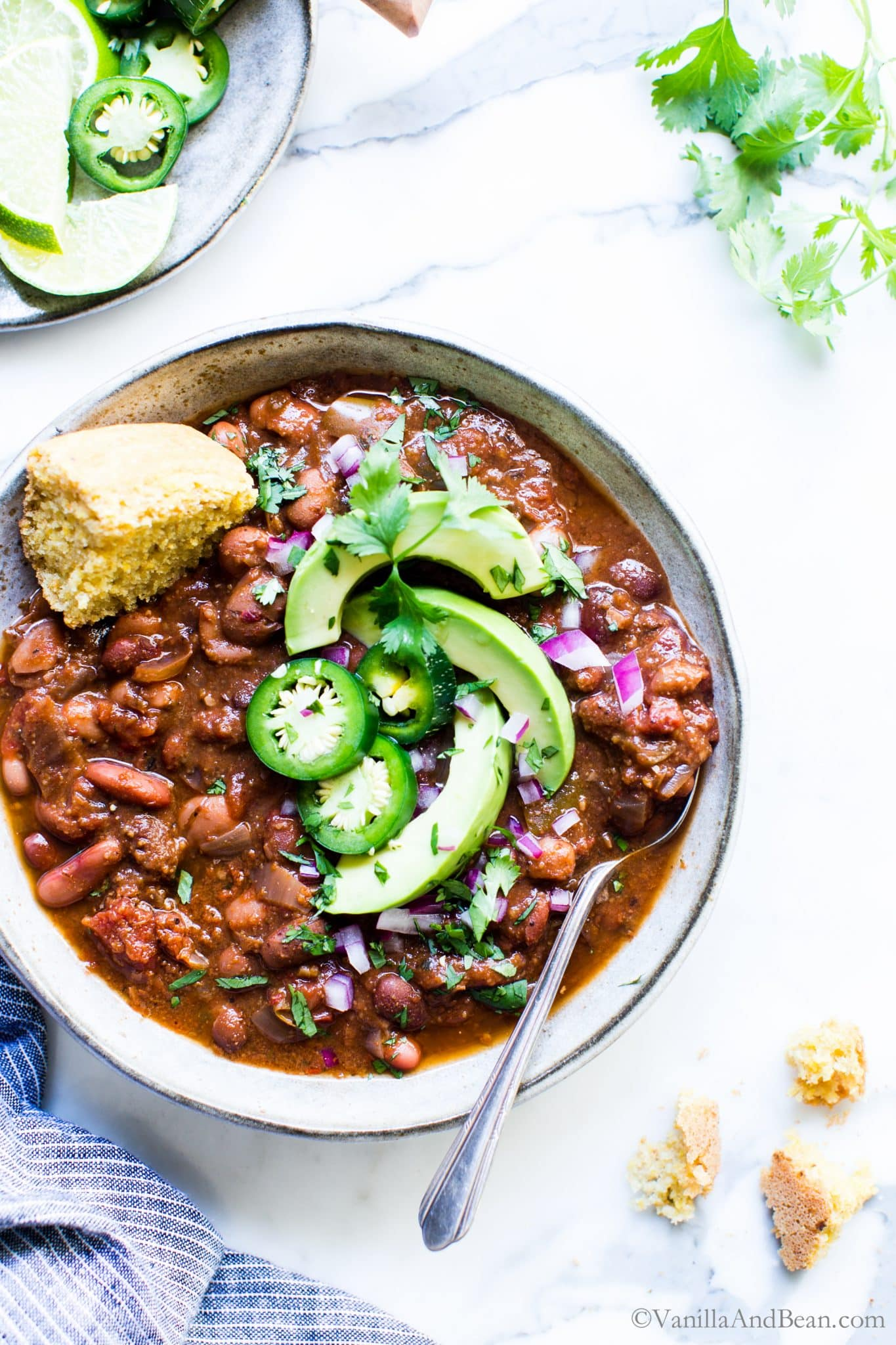 Vegetarian Chili in a bowl garnished with avocado, peppers and shared with cornbread.