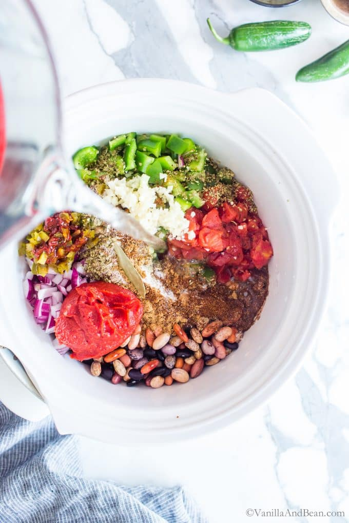Pouring water in a a crock pot filled with vegetarian chili ingredients.