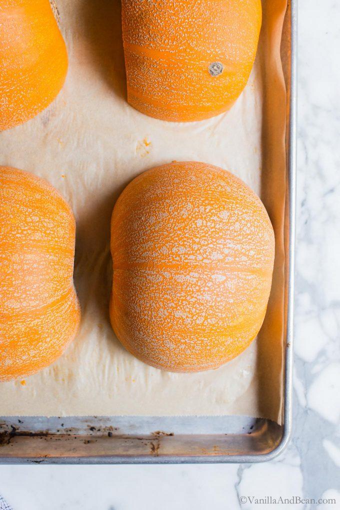 Pumpkins flesh side down on a parchment lined sheet pan.