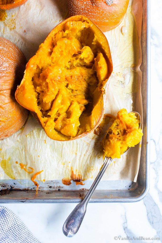 Scooping out the flesh of a roasted pumpkin.