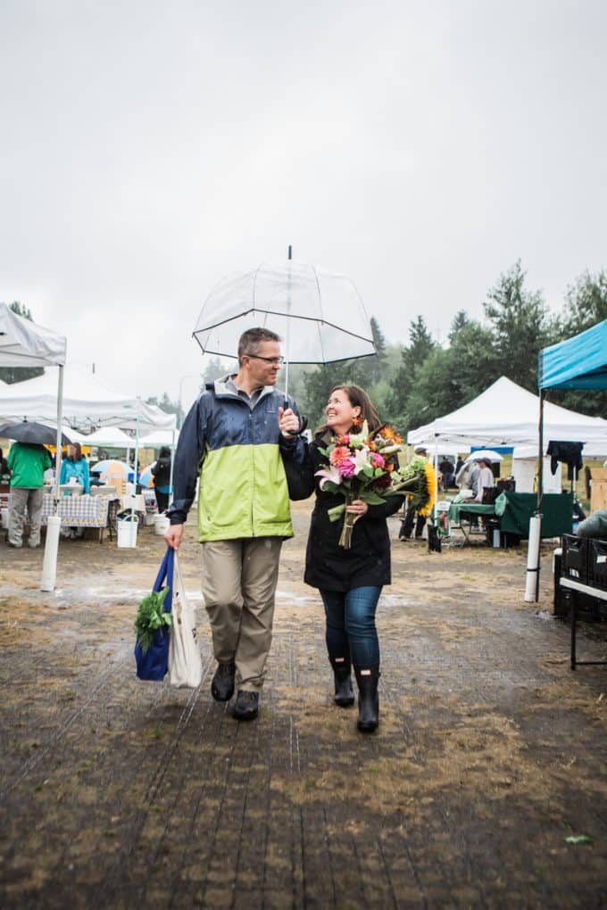 Traci with her husband at the farmers market under an umbrella holding bags and flowers.