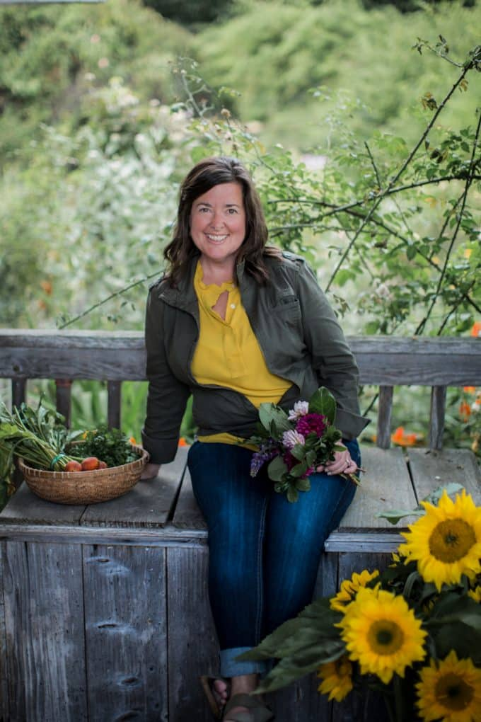 Traci sitting on bench at the farm holding flowers, smiling.