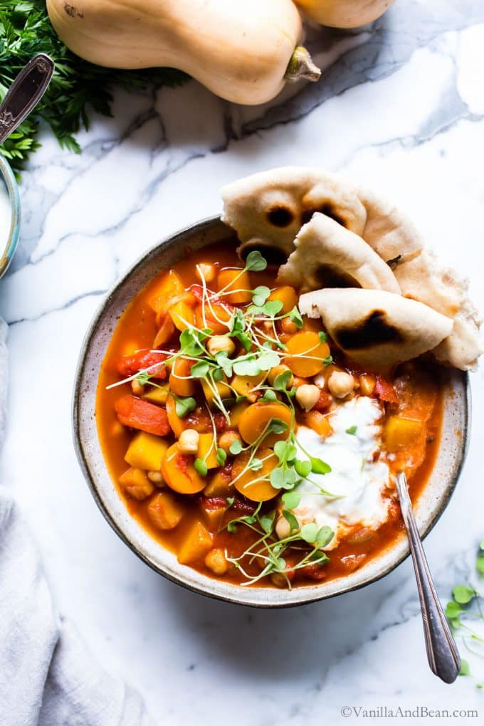 Moroccan Butternut Squash Stew topped with yogurt, microgreens and shared with Naan in a bowl.
