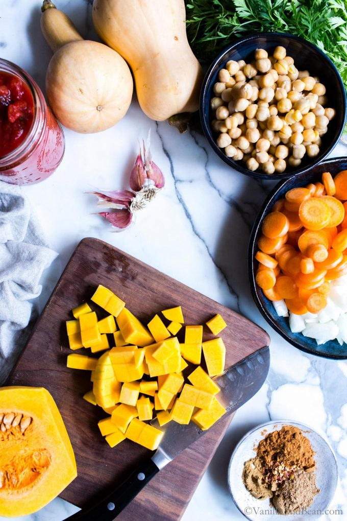 Chopped Butternut Squash on a cutting board with other ingredients for the stew.