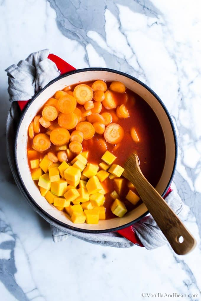 Adding the butternut squash, carrots and tomatoes to the Dutch oven.
