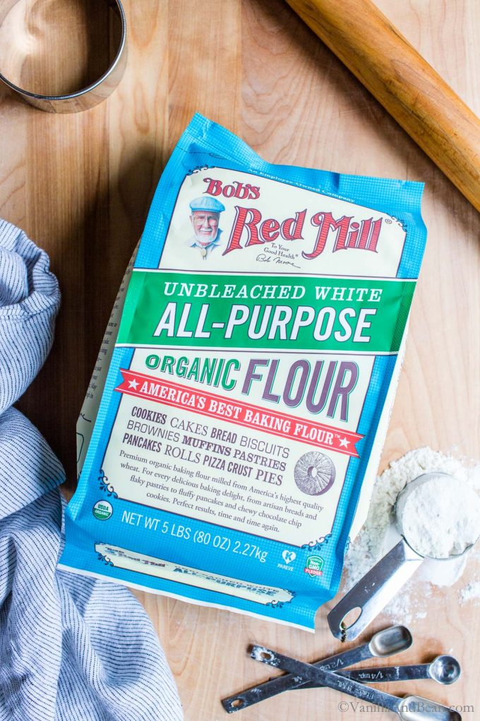 A bag of all purpose flour on a baking board.